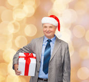 Smiling man in suit and santa helper hat with gift Stock Image