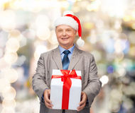 Smiling man in suit and santa helper hat with gift Royalty Free Stock Photo