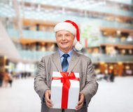 Smiling man in suit and santa helper hat with gift Royalty Free Stock Photos