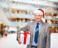 Smiling man in suit and santa helper hat with gift Royalty Free Stock Images