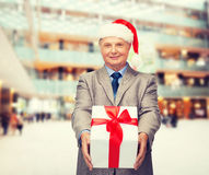 Smiling man in suit and santa helper hat with gift Stock Photos