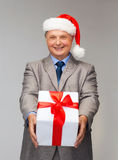 Smiling man in suit and santa helper hat with gift. Business, christmas, xmas, happiness concept - smiling old man in suit and santa helper hat with gift Royalty Free Stock Photo