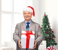 Smiling man in suit and santa helper hat with gift Royalty Free Stock Image