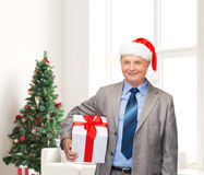 Smiling man in suit and santa helper hat with gift Stock Photography