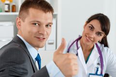 Smiling man in suit showing OK sign with thumb up Royalty Free Stock Image