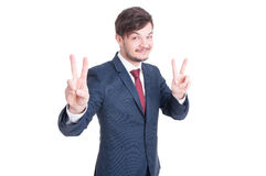 Smiling man in suit showing peace sign Royalty Free Stock Photos