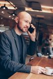 The smiling man in suit speaking on mobile phone, sitting with coffee at cafe royalty free stock photography