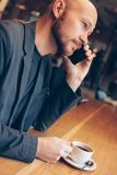 The smiling man in suit speaking on mobile phone, sitting with coffee at cafe royalty free stock photos