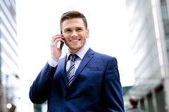 Smiling man in suit talking on cell phone Stock Photography
