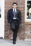 Smiling Man in Suit and Tie. Smiling Man Dressed in Suit and Tie Leaning against Brick Wall Royalty Free Stock Photography