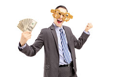 Smiling man in suit wearing dollar glasses and holding dollars Stock Photos