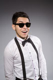 Smiling man in sunglasses against gray Stock Photo