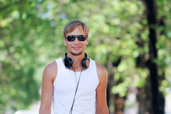 Smiling man in sunglasses and headphones on alley Royalty Free Stock Photography
