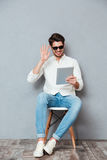 Smiling man in sunglasses using tablet and having videoconference Royalty Free Stock Photography