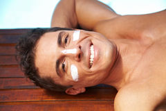 Smiling man with sunscreen on face Stock Photography