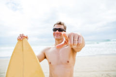 Smiling man with surfboard at beach pointing with finger. Focus on pointing finger of married smiling male surfer with surfboard at beach Royalty Free Stock Images