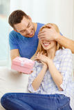 Smiling man surprises his girlfriend with present Royalty Free Stock Images