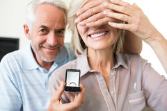 Smiling man surprising woman with a wedding ring Royalty Free Stock Photos