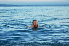 Smiling man swims in the sea at dawn Royalty Free Stock Photos