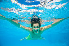 Smiling man swims under the crystal-clear water Royalty Free Stock Images