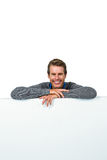 Smiling man on table against white background Stock Photos
