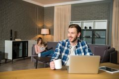 Smiling man at table with laptop and woman reading book on couch in modern. Living room royalty free stock photos