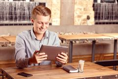 Smiling man with tablet in cafe Stock Photography