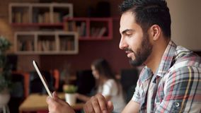 Smiling man with tablet. Good-looking fit man using tablet, having time off in modern european cafe, smiling joyfully as relaxing with newest technological stock video