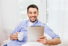 Smiling man with tablet pc and cup at home. Technology, people and leisure concept - handsome man with tablet pc computer and cup drinking coffee or tea at home Stock Image