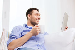 Smiling man with tablet pc and cup at home Stock Image