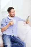 Smiling man with tablet pc and cup at home Royalty Free Stock Image