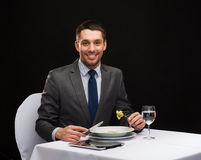 Smiling man with tablet pc eating main course Royalty Free Stock Photography