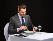 Smiling man with tablet pc eating main course Royalty Free Stock Photo