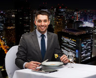 Smiling man with tablet pc eating main course Stock Photos