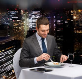 Smiling man with tablet pc eating main course Royalty Free Stock Images