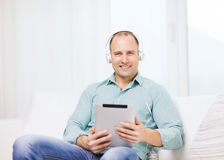 Smiling man with tablet pc and headphones at home Stock Image