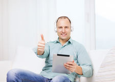 Smiling man with tablet pc and headphones at home Royalty Free Stock Photos