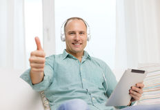 Smiling man with tablet pc and headphones at home Stock Images