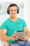 Smiling man with tablet pc and headphones at home Royalty Free Stock Photo