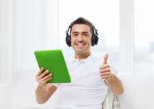 Smiling man with tablet pc and headphones at home Royalty Free Stock Image