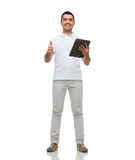 Smiling man with tablet pc showing thumbs up Royalty Free Stock Photo
