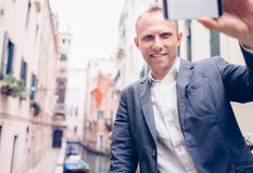 Smiling man take a selfie tourist photo on the Venice chanel bac Royalty Free Stock Photos