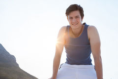 Smiling man taking break after jogging on beach Royalty Free Stock Images