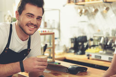 Smiling man taking coffee in comfortable candy store. Cheerful worker drinking glass of latte while standing near cash desk. Various appliances are around waiter Stock Image