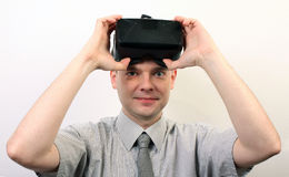A smiling man taking off or putting on Oculus Rift VR virtual reality headset,  positively impressed Royalty Free Stock Photography