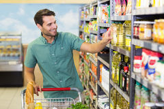 Smiling man taking a oil in the aisle Royalty Free Stock Images