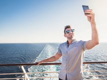 Smiling man taking selfie on the open deck stock images