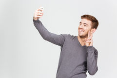 Smiling man taking selfie with smartphone and showing peace sign. Smiling attractive young man in grey pullover taking selfie with smartphone and showing peace royalty free stock image