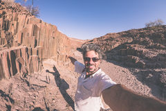 Smiling man taking selfie at volcanic rock formation known as royalty free stock photos