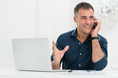 Smiling Man Talking On Cellphone. Portrait Of Happy Mature Man In Front Of Laptop Talking On Cellphone Stock Images